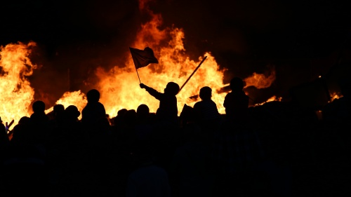 People at a riot burning items.