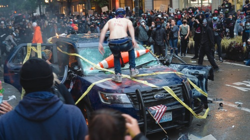 Rioters destroy a police vehicle in Seattle.
