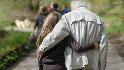 Photo of a young girl on the left and old man on the right, walking along a paved trail in a park, each with an arm around the other.