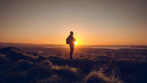 A man standing on a hill with the sun setting.