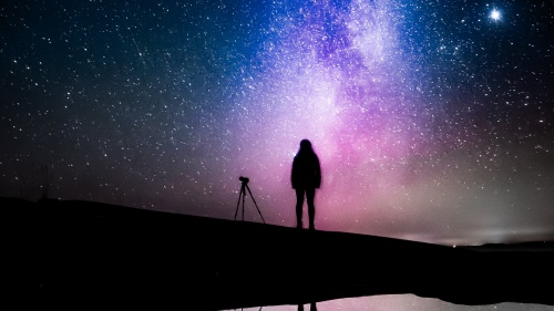 Silhouette of a person with a telescope against a gorgeous starry sky
