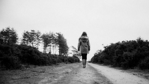 A woman walking on a dirt road.