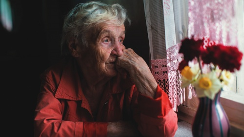 An older women sitting by a window looking outside.