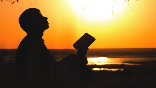 A person holding a Bible and looking up to the sky.