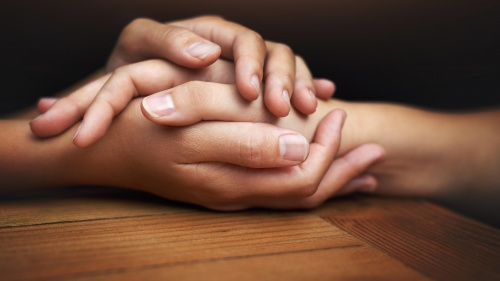 Two people's hands touching and showing comfort.