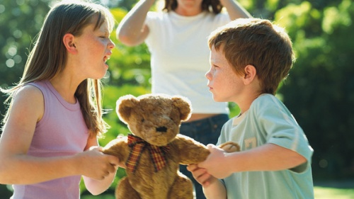 Two siblings fight over a stuffed teddy bear with the mom in the background.