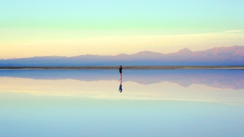 Photo of a person walking along the beach at low tide with their reflection in the water below.