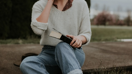 A girl in cropped mom jeans sits on the ground with a Bible in her lap. A wide brim hat sits next to her and she has a flowery collared shirt on under a white sweater.