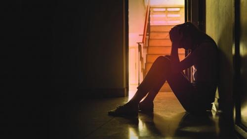 A sad woman sitting on the floor in a hallway.