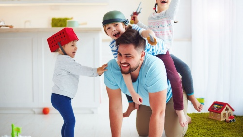 A dad playing with his kids.