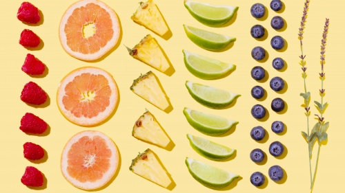 Rows of fruit aligned geometrically including pineapples, blueberries, raspberries and limes