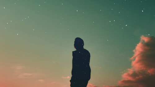 Silhouetted person against a dramatic, colorful sunset sky, with the person's silhouette filled with a different background, of a starry sky.
