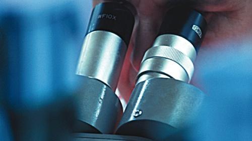 A scientist using a microscope.
