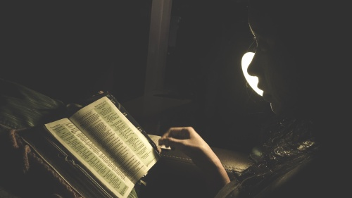 A person reading a Bible by a lamp.