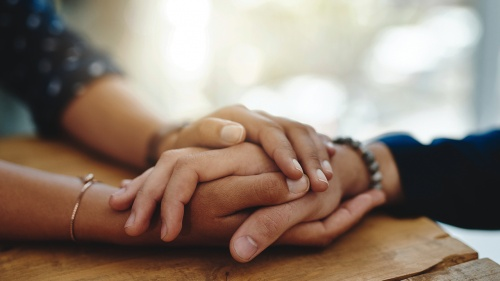 Comforting hands of two people.
