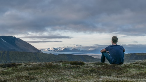 A man sitting on the ground looking at the scenery.