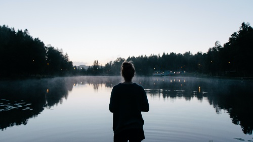 A woman looking at a lake.