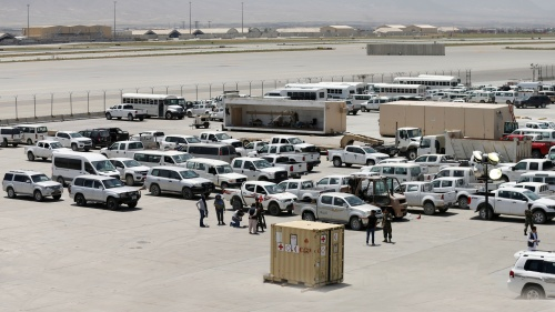 Afghan soldiers inspect some of the thousands of U.S. vehicles abandoned in the American pullout from Bagram Air Base, Afghanistan, in July 2021.