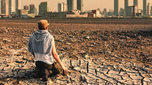 A person sitting on dry barren dirt.