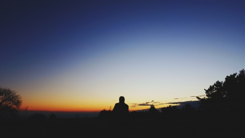 A person sitting at the top of hill looking at the expanse of the night sky.