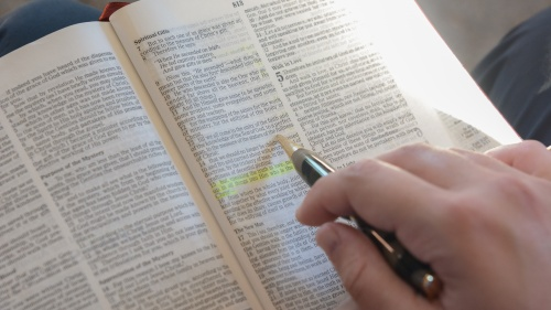 A photo of a hand highlighting a scripture in the Bible.