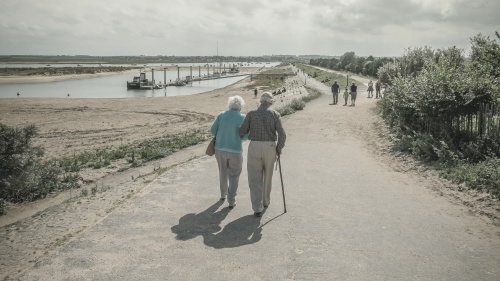 An elder couple walking together on a paved path.