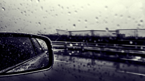 Car side mirror raining outside.
