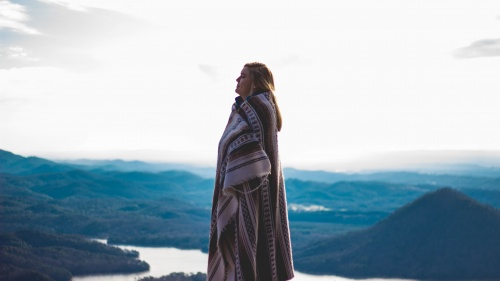 A woman wrapped in a blanket standing outside with mountains in the background.