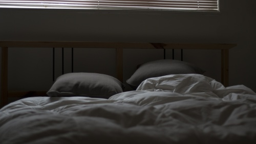 A bed in a dark room.