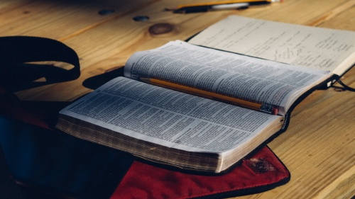 An open Bible on a table with a notebook and pencils and pens.