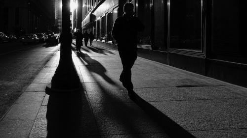 A person walking on a sidewalk at night.