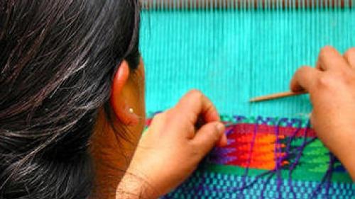 A woman weaving on a loom.