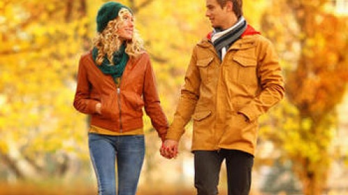 A man and woman holding hands walking in a park in the fall.