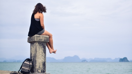 woman sitting on post looking at water