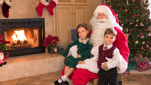 Two children sitting with Santa Claus in front of a Christmas tree.