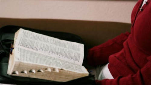A woman reading a Bible on her lap.