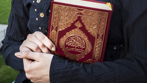 Woman holding a copy of the Quran in her arms.