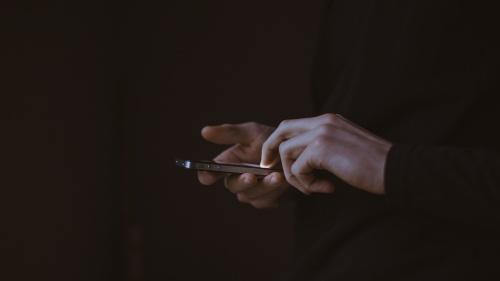 A person using a smartphone in the dark.