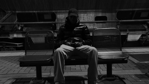 A person sitting along on a bench.