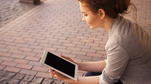 A young woman reading on a tablet device.