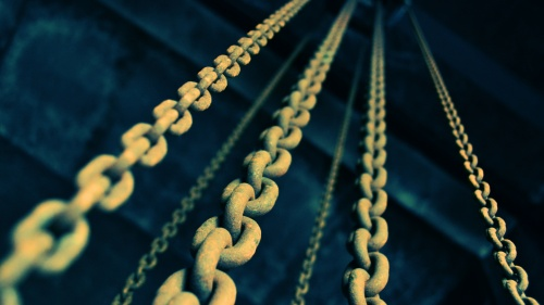 Old chains hanging down from a dark ceiling.