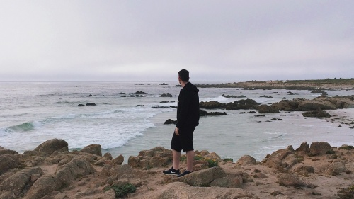 A man walking on a rocky shore of the ocean.