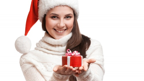 A woman wear a Christmas stocking cap holding a gift.