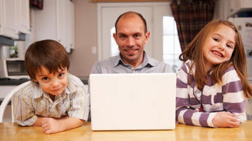 A dad sitting with two kids at a table.