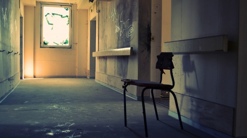 A lone student desk in a old run down school hallway.