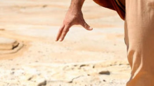 A stone falling from a man's hand.