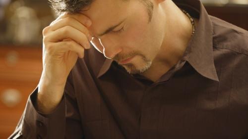 A man praying over his Bible