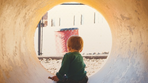 A little boy in a large concrete drain tube playing.