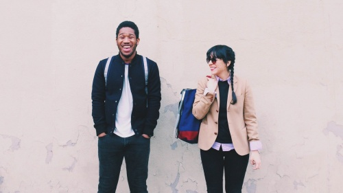 Two young adults waiting for a bus - both with smiles on the faces.