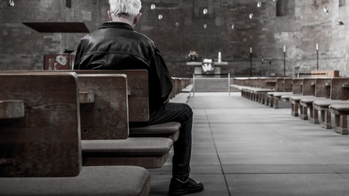 A old man sitting in a pew in an old church.